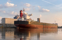 Bulk carrier moored at the quay, and busy with cargo operations. stock photo