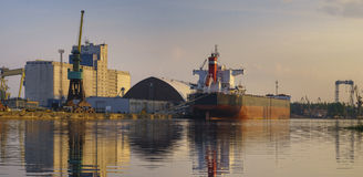 Bulk carrier moored at the quay, and busy with cargo operations. royalty free stock images