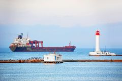 Bulk carrier near lighthouse. In Odessa, Ukraine stock photography
