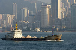 Bulk carrier passing skyscrapers of Hong Kong Royalty Free Stock Image