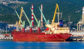 A bulk carrier in a port. Bulk freighter, or colloquially, bulker is a merchant ship specially designed to transport unpackaged bulk cargo, such as grains stock photo