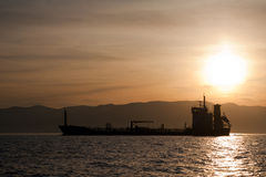 Bulk-carrier ship at sunset. In the sea royalty free stock photo