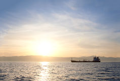 Bulk-carrier ship at sunset. In the sea stock photos