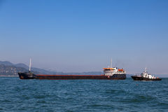 Bulk-carrier ship and tugboat Royalty Free Stock Images