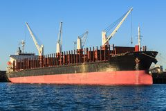 Bulk carrier vessel ship in port. A large bulk carrier ship docked beside a wharf. The raised stanchions, the bars at the side of the ship, show that it is set royalty free stock images
