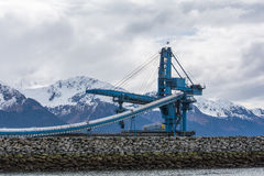 Bulk Coal Ship Loader Idle. A blue and white bulk coal loader stands idle awaiting the next ship in an Alaska harbor with mountains in the background stock image