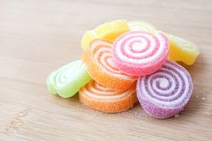 Bulk of colorful gummy jelly candy rolls with sugar, Put on wood. Bulk of colorful gummy jelly candy rolls with sugar royalty free stock photo