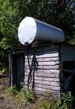 Bulk fuel tank on old sqare log oil shack. A typical structure in rural farm yards in South Central Manitoba where farmers would pull up to refuel their tractors Royalty Free Stock Image