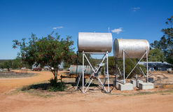Bulk Fuel. Two elevated barrel fuel tanks in Western Australia farmland with trees and sandy ground under a clear blue sky Stock Photos