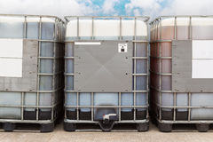 Bulk oil container. Bulk plastic oil containers with metallic cage in storage area stock photo