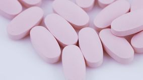 Oval pink tablets on plate stock video