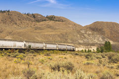 Bulk rail cars rolling across the grasslands. Bulk rail cars of the Canadian National Railway rolling across the grassland in the interior of BC, Canada Stock Photography