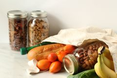 Bulk shopping. Concept. Glass replacing plastic containers. Fresh groceries spill out of reusable grocery bag. Copy space royalty free stock image