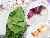 Bulk vegetables, fruit and mushrooms. Bulk onions, apples, lettuce and mushrooms in reusable cotton bags royalty free stock photo