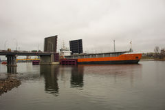 Bulker vessel entering the port, passing the vertical lift bridge Royalty Free Stock Photography
