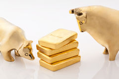 Bull and bear markets symbols with gold bars Royalty Free Stock Images