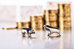 Bull market on the stock market. Bull and bear with stacks of coins and stock prices in the background royalty free stock photos
