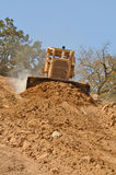Bull Dirt. Large bulldozer moving rock and soil for fill for a new commercial development road construction project Stock Photo
