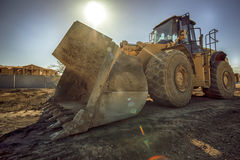 Bull Dozer on a constructions site. With lens flare stock images