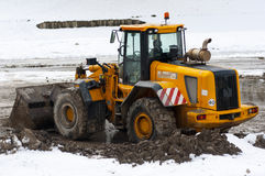Bull dozer deep in mud and snow. Image of a bulldozer deep in mud and snow Stock Photography