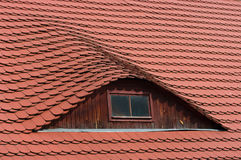 Bull eye roof window. Detail of a red roof with bull eye window Stock Image