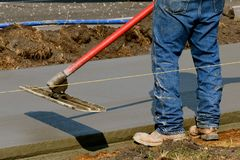 Bull float being used on a freshly poured sidewalk Stock Photography