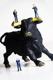 Bull market. Business figurines placed on a bull figurine Royalty Free Stock Photography