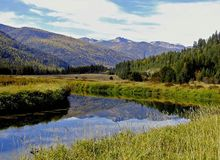 Bull River Reflection. This image of the Bull River with the mountains and tamaracks reflected was taken in extreme NW Montana Stock Photo