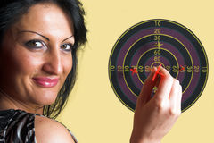 Bull's-eye. Woman holding a red dart over a center of a target Royalty Free Stock Photos