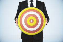Bull's-eye concept with businessman holds a dart Royalty Free Stock Images