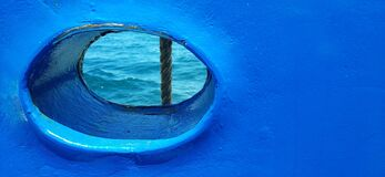 Bull´s eye, porthole, round window on a blue boat, ship, ferry