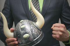 Bull stock broker. Bull market concept. Agressive business strategy. Business man holding a toy viking helmet in hands. Boosting price game on the stock Stock Image