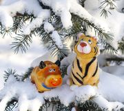 Bull and tiger on snow-bound firry branches. Figurines bull and tiger symbols of 2009 and 2010 years Stock Images