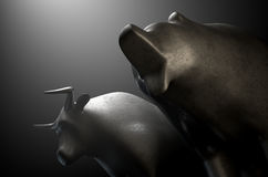 Bull Versus Bear. A closeup of two metal castings depicting a stylized bull alongside a bear in dramatic light representing  financial market trends on an Royalty Free Stock Photography