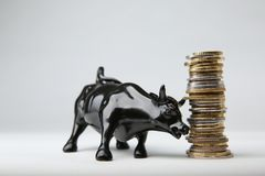 Bull from wall street butts a pillar of coins. On white background. stock bull next to a column of coins stock image
