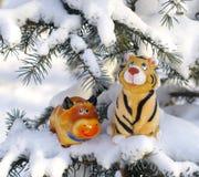 Bull y tigre en ramificaciones firry sitiadas por la nieve Imagenes de archivo