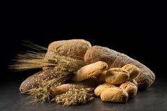 Bullar, bagett, ciabatta och bröd på den mörka trätabellen Råg, korn, vete, havre och många nya blandade bröd på svarta lodisar Arkivfoto