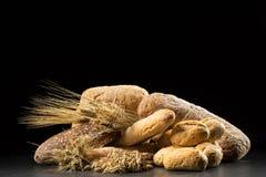 Bullar, bagett, ciabatta och bröd på den mörka trätabellen Råg, korn, vete, havre och många nya blandade bröd på svarta lodisar Royaltyfri Foto