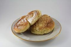 Bullar i pudrat socker på en vit maträtt på en vit bakgrund arkivfoton