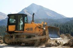 Bulldozer. In mountain with road Stock Photos
