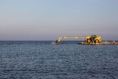 Bulldozer. Being used to construct sea defenses on the beach Royalty Free Stock Photo
