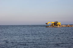 Bulldozer. Being used to construct sea defenses on the beach Stock Photo
