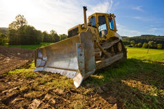 Bulldozer. Yellow bulldozer in action in field Royalty Free Stock Image