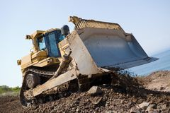 Bulldozer. The bulldozer on a building site.On a background the sea Stock Photography