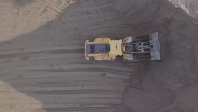 Bulldozer in action in open air quarry. Original LOG. Aerial view loading bulldozer in open air quarry. Original untouched LOG format stock video footage