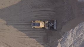Bulldozer in action in open air quarry. Untouched LOG format. Aerial view loading bulldozer in open air quarry. Original untouched LOG format stock footage