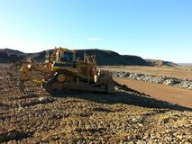 Bulldozer battering down slope of waste dump at mine Stock Photo