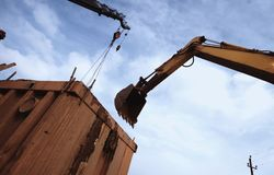 Bulldozer bucket above the container. The bulldozer is digging royalty free stock photo