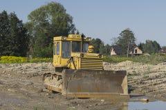 Bulldozer at building construction site. Old rusty earth digging caterpillar bulldozer machine working at building construction site in Poland Royalty Free Stock Photo