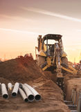 Bulldozer carving hole for pipe laying on constructions site. End of work day sunset Royalty Free Stock Photography